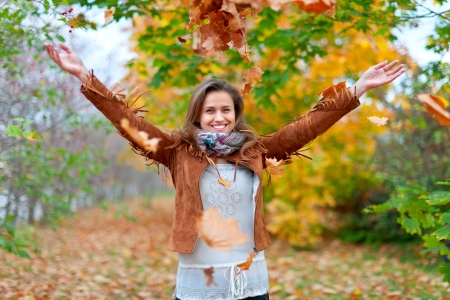 Happy girl throws maple leaves in autumn park photo