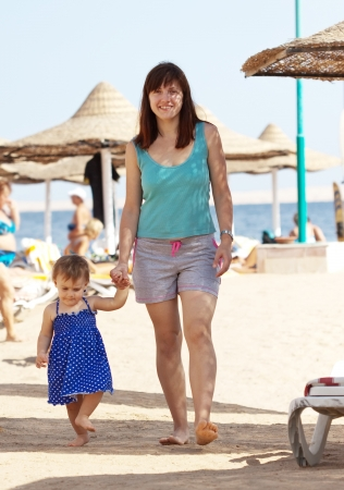 toddler walking: young mother with adorable toddler walking on beach