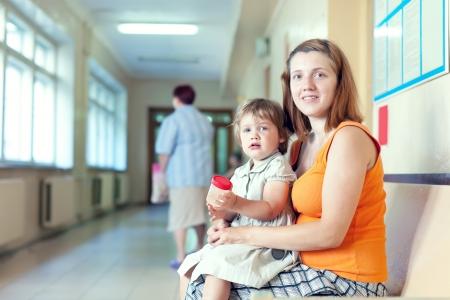 urinalysis: donna incinta e il bambino con il campione delle urine presso la clinica