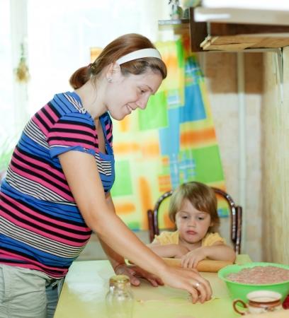 gravida: pregnant woman with child making russian meat dumplings (pelmeni)