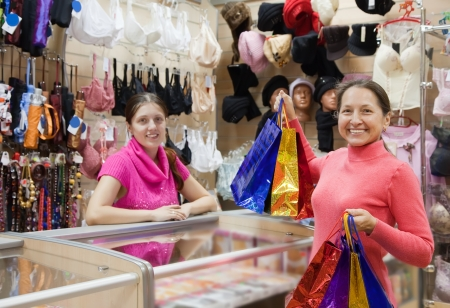 Female mature buyer with shopping bags at  counter  in  shop. Focus on buyer Stock Photo - 15639879