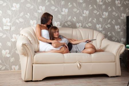 women lying on sofa in livingroom with TV Remote control photo