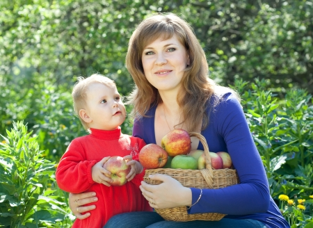Happy family with apples harvest in garden photo