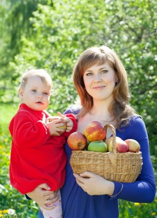 family with  harvested apples in garden photo