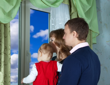 Family  looking out the window in home Stock Photo - 15640833