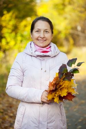 Portrait of happy mature woman  in autumn park Stock Photo - 15691263
