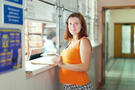 Pregnant woman waiting  for patient's records in clinic reception desk Stock Photo - 15720245
