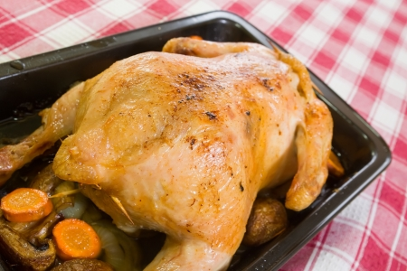 roasting pan: stuffed chicken In roasting pan on checked tablecloth