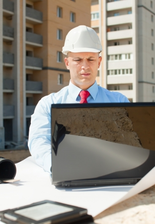 Portrait of white-collar worker wearing protective helmet works on the building site photo