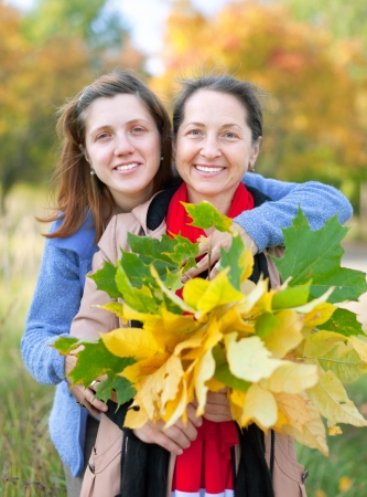Happy  mature woman with adult daughter in autumn  park photo