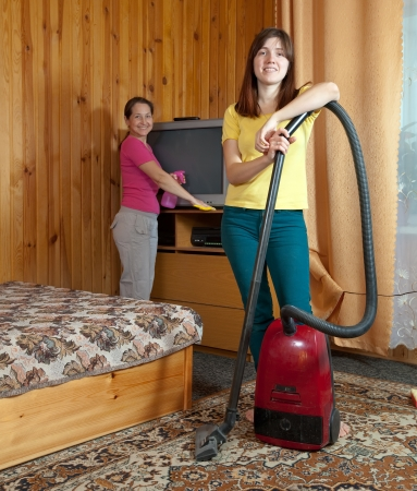 Women cleaning with vacuum cleaner in living room Stock Photo - 15752952