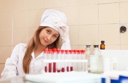 weariness: cansancio enfermera trabaja con muestra de sangre en laboratorio m�dico Foto de archivo