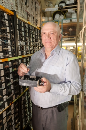 mature man chooses hardware in  auto spare parts store Stock Photo - 15747230