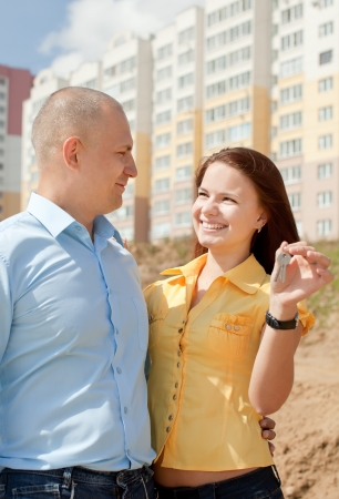 Outdoor portrait of   happy couple against real estate Stock Photo