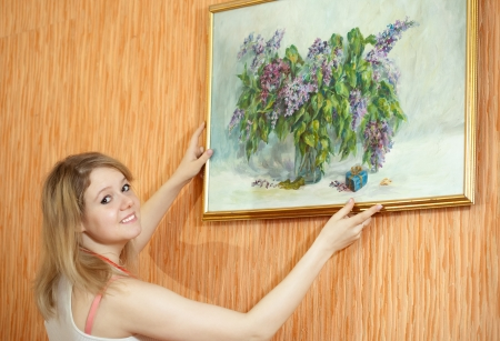 hangs: Young woman  hangs the art picture on wall at home Stock Photo