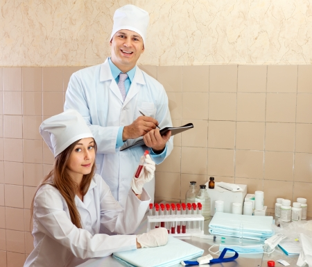 Male doctor and nurse with test tubes makes blood test in medical laboratory Stock Photo - 15831851