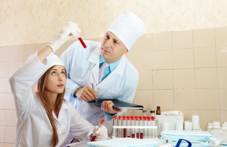 Male doctor and nurse with test tubes makes blood test in medical laboratory Stock Photo - 15831827