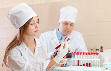 Young nurse and male doctor with test tubes making haemanalysis Stock Photo - 15831826