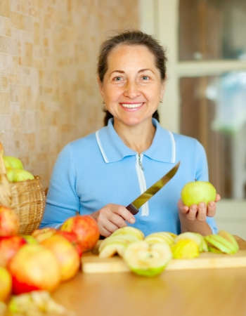 Woman cuts apples for apple jam in kitchen photo