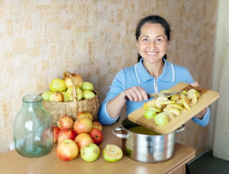 Woman cooks apple jam in the kitchen photo