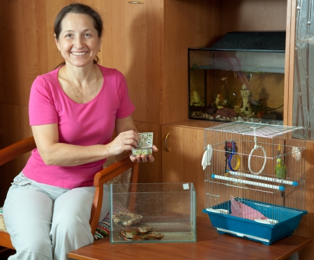 aquaria:   woman feeds pets  in home