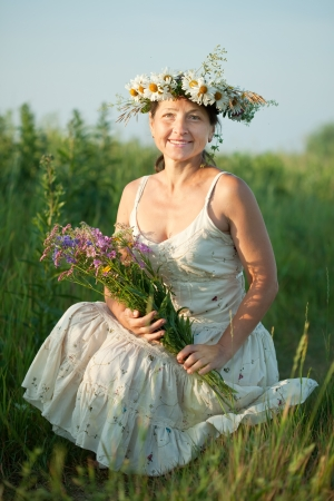 gathers: Mature woman gathers herbs at wild meadow