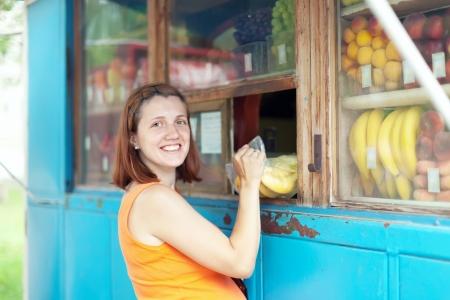 gravida:  woman buys fruits at market Stock Photo