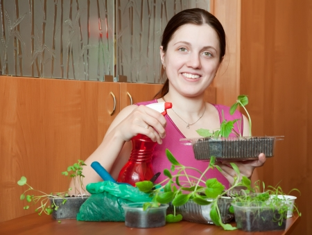 Happy girl with various seedlings at home photo