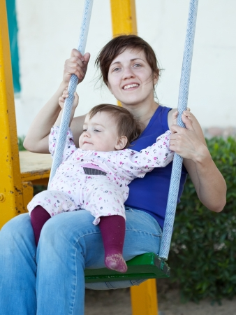 happy mother with  toddler at playground area photo