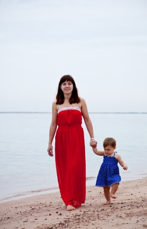 full length shot of mother with  toddler walking  on sand beach Stock Photo - 15870323