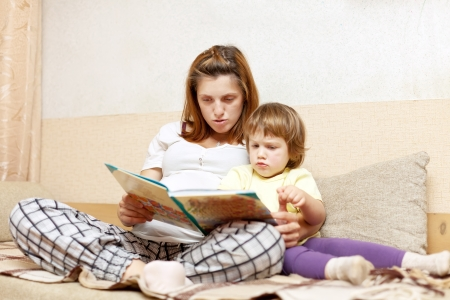 Mother and daughter reading  book together on couch in home photo