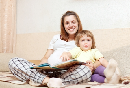 pregnant woman and daughter reads  book together on couch in home photo