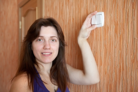 Young woman with light-switch in home photo