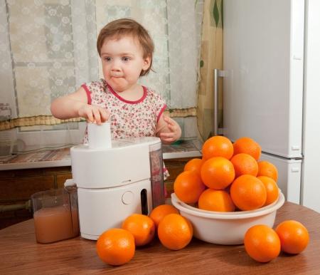 Baby girl making fresh orange juice in home kitchen photo