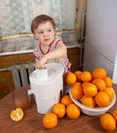 Baby girl making fresh orange juice in kitchen photo
