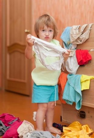 get dressed: Baby girl at wardrobe. She thinking what get dressed Stock Photo