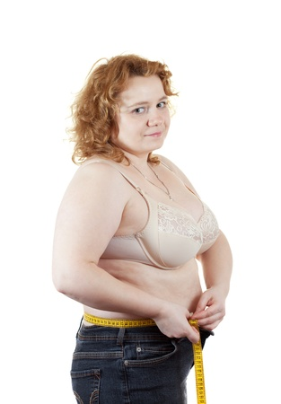 fat unsightly woman measuring waist with tape measure  Isolated over white background photo