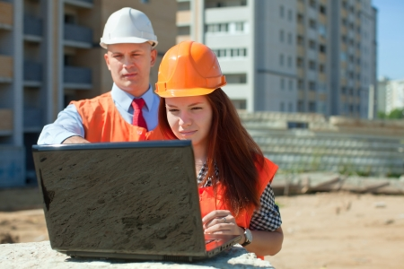 two builders wearing protective helmet works on the building site Stock Photo - 15870664