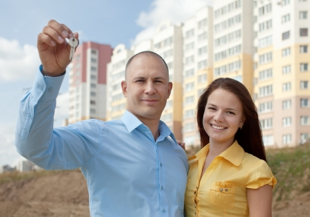 residential settlement: Happy couple with key against building new brick house