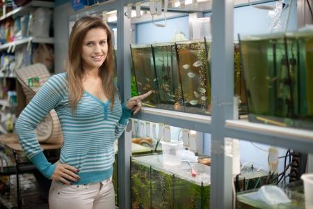 fish store: La mujer elige peces en acuarios de pet-shop