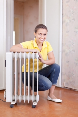 Happy woman near oil heater in home photo
