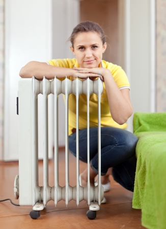 calorifer:  Happy woman near oil heater in home