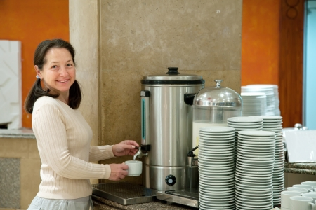 Woman pours  coffee from  coffee machine  Stock Photo - 15929941