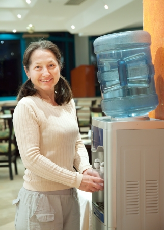 Woman pours   water from water cooler  photo