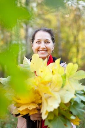 Portrait of happy mature woman  in autumn park Stock Photo - 15940324