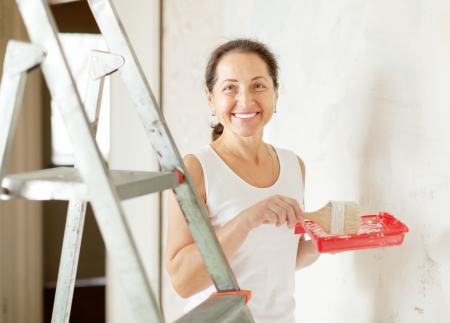 housepainter: Happy mature woman paints wall with brush at home Stock Photo