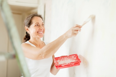 priming brush: Happy mature woman paints wall with brush at home Stock Photo