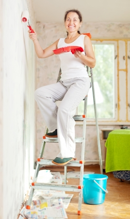 Happy woman paints wall with roller at home Stock Photo - 15940319