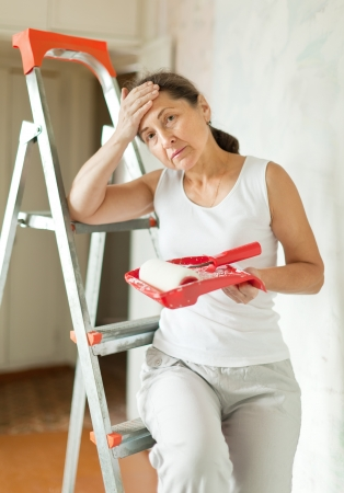 weariness mature woman makes repairs at home photo