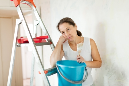 priming brush: weariness mature woman makes repairs at home